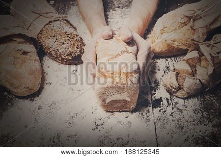 Lots of different bread sorts, wrapped in craft paper. Baking and cooking concept background. Hands of baker carefully hold loaf on wooden table, sprinkled with flour. Filtered image