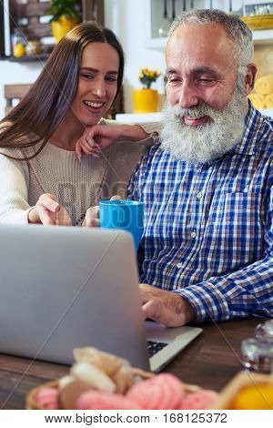 Close-up of couple working together at home. Woman holding her hand over shoulder of her friend. Trying to explain some working details. They are sitting at the table, using netbook