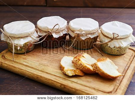 Close-up of opened jars with ready-to-it food standing on the wooden board. Lunchtime food. Portable jars