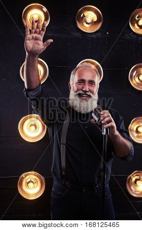 Mid shot of pleased singer welcoming funs while performing a jazz song on the stage. Live performance of exhilarated male singer holding silver vintage microphone