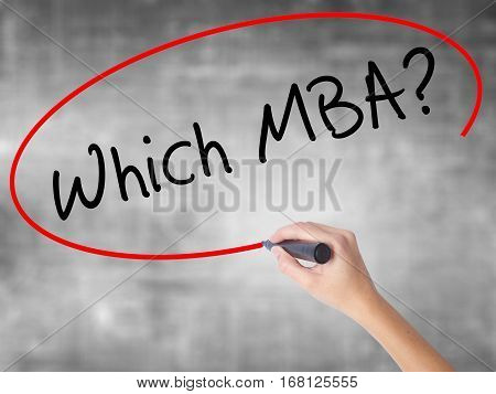 Woman Hand Writing Which Mba? With Black Marker Over Transparent Board