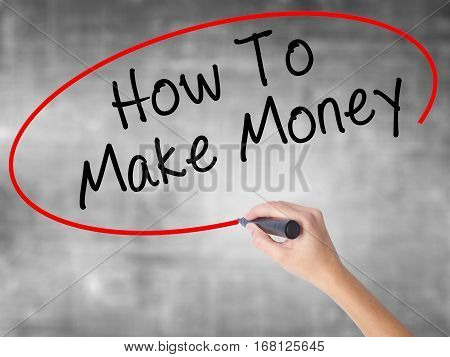 Woman Hand Writing How To Make Money With Black Marker Over Transparent Board
