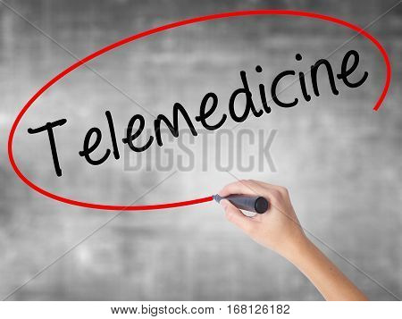 Woman Hand Writing Telemedicine With Black Marker Over Transparent Board