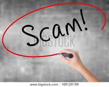 Woman Hand Writing  Scam! With Black Marker Over Transparent Board