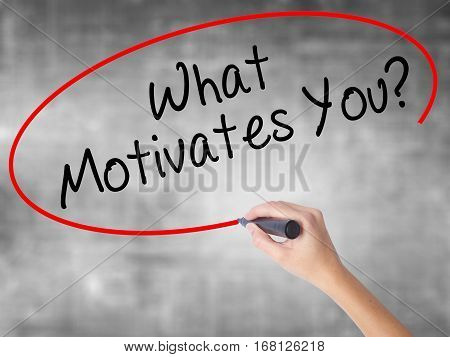 Woman Hand Writing What Motivates You? With Black Marker Over Transparent Board