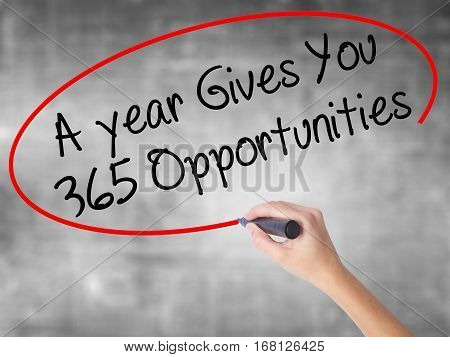 Woman Hand Writing A Year Gives You 365 Opportunities With Black Marker Over Transparent Board