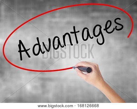 Woman Hand Writing Advantages With Black Marker Over Transparent Board
