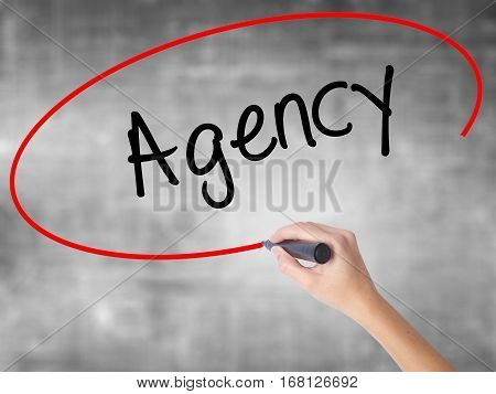 Woman Hand Writing Agency With Black Marker Over Transparent Board