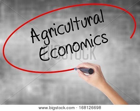 Woman Hand Writing Agricultural Economics With Black Marker Over Transparent Board