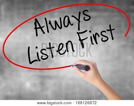 Woman Hand Writing Always Listen First With Black Marker Over Transparent Board
