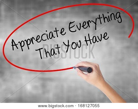 Woman Hand Writing Appreciate Everything That You Have With Black Marker Over Transparent Board.