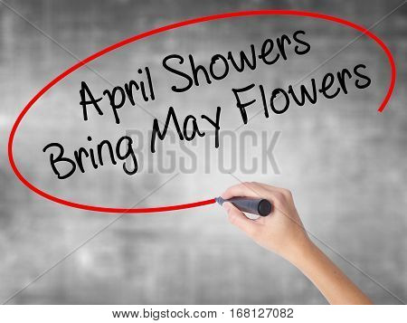 Woman Hand Writing April Showers Bring May Flowers With Black Marker Over Transparent Board