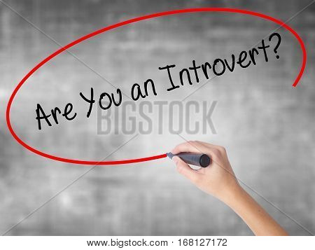 Woman Hand Writing Are You An Introvert? With Black Marker Over Transparent Board