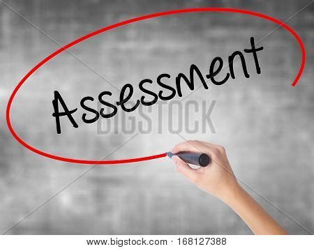 Woman Hand Writing Assessment With Black Marker Over Transparent Board