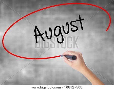 Woman Hand Writing August  With Black Marker Over Transparent Board