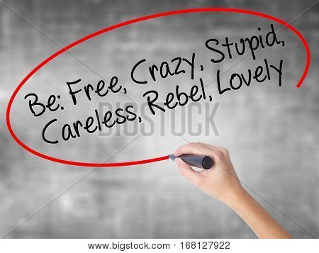Woman Hand Writing Be: Free, Crazy, Stupid, Careless, Rebel, Lovely With Black Marker Over Transpare