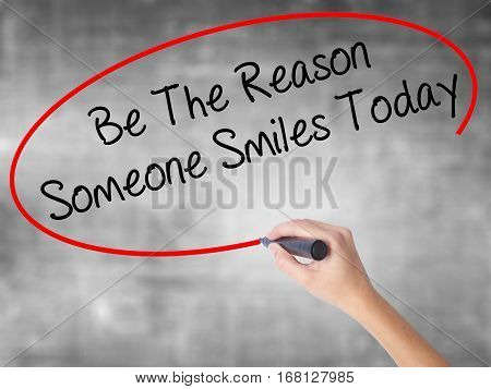 Woman Hand Writing Be The Reason Someone Smiles Today  With Black Marker Over Transparent Board