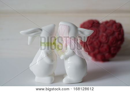 Two cute ceramic rabbits in love on the white wooden background. St. Valentine's Day. kiss. February 14.
