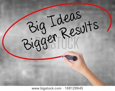 Woman Hand Writing Big Ideas Bigger Results  With Black Marker Over Transparent Board