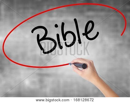 Woman Hand Writing Bible With Black Marker Over Transparent Board