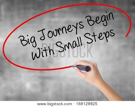 Woman Hand Writing Big Journeys Begin With Small Steps  With Black Marker Over Transparent Board