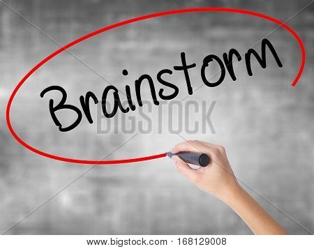 Woman Hand Writing Brainstorm With Black Marker Over Transparent Board.
