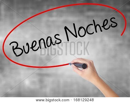 Woman Hand Writing Buenas Noches (good Night In Spanish) With Black Marker Over Transparent Board.