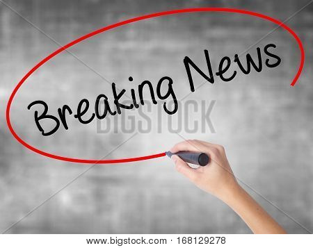 Woman Hand Writing Breaking News With Black Marker Over Transparent Board