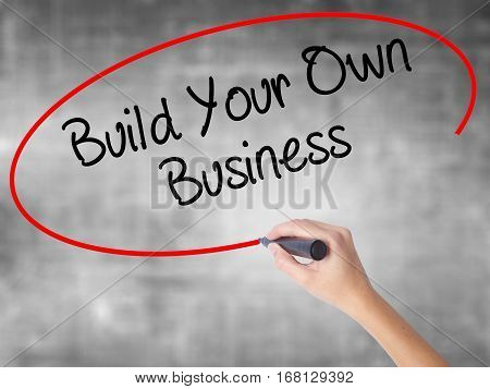 Woman Hand Writing Build Your Own Business With Black Marker Over Transparent Board.