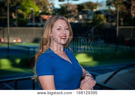 Fair skinned red head woman smiling while wearing blue polo shirt.