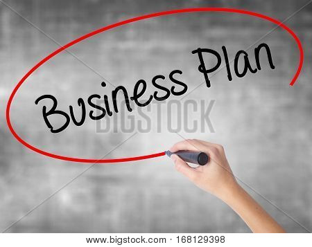 Woman Hand Writing  Business Plan With Black Marker Over Transparent Board