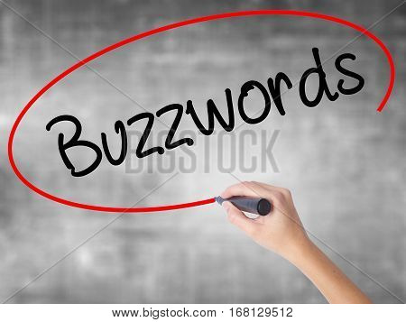 Woman Hand Writing Buzzwords With Black Marker Over Transparent Board