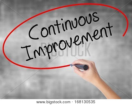 Woman Hand Writing Continuous Improvement With Black Marker Over Transparent Board