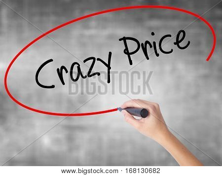 Woman Hand Writing Crazy Price With Black Marker Over Transparent Board