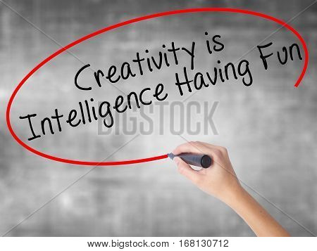 Woman Hand Writing Creativity Is Intelligence Having Fun With Black Marker Over Transparent Board