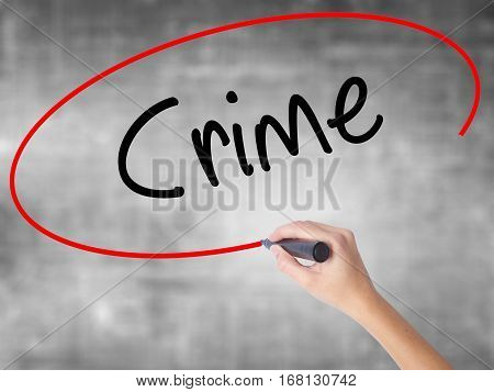Woman Hand Writing Crime With Black Marker Over Transparent Board