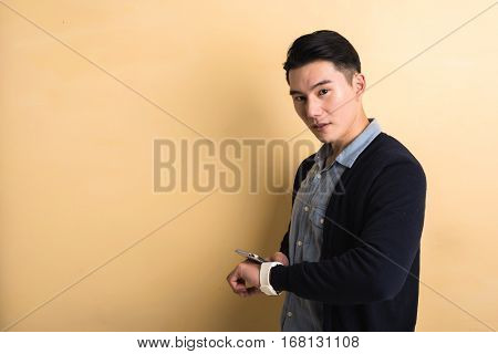 handsome Asian young man using smart watch and phone, shot at studio yellow background