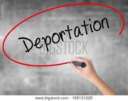 Woman Hand Writing Deportation  With Black Marker Over Transparent Board