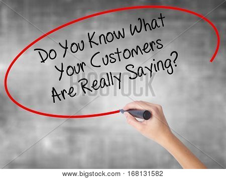 Woman Hand Writing Do You Know What Your Customers Are Really Saying? With Black Marker Over Transpa