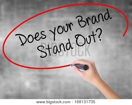 Woman Hand Writing Does Your Brand Stand Out? With Black Marker Over Transparent Board