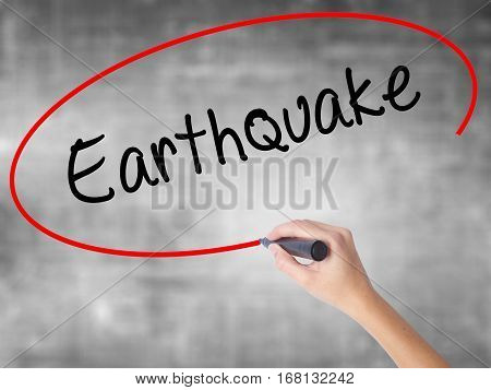 Woman Hand Writing Earthquake With Black Marker Over Transparent Board