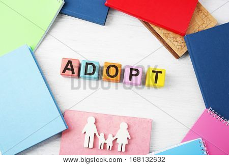 Colorful cubes with word ADOPT, figure in shape of family and notepads on wooden background