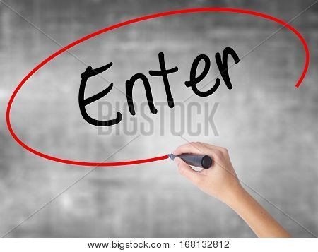 Woman Hand Writing Enter With Black Marker Over Transparent Board