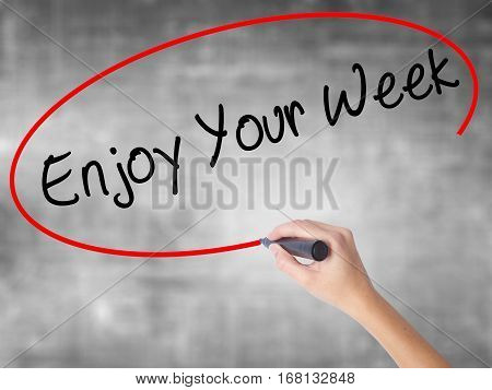 Woman Hand Writing Enjoy Your Week With Black Marker Over Transparent Board