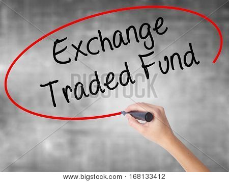 Woman Hand Writing Exchange Traded Fund With Black Marker Over Transparent Board.