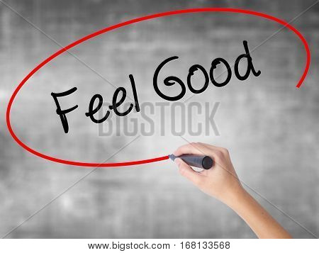 Woman Hand Writing Feel Good With Black Marker Over Transparent Board