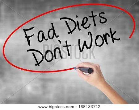 Woman Hand Writing Fad Diets Don't Work With Black Marker Over Transparent Board