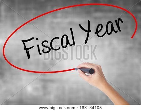 Woman Hand Writing Fiscal Year With Black Marker Over Transparent Board.