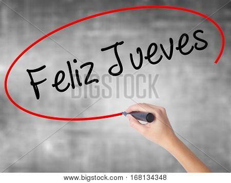 Woman Hand Writing Feliz Jueves (happy Thursday In Spanish) With Black Marker Over Transparent Board