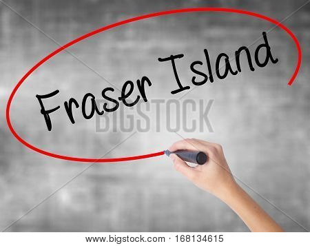 Woman Hand Writing Fraser Island With Black Marker Over Transparent Board.